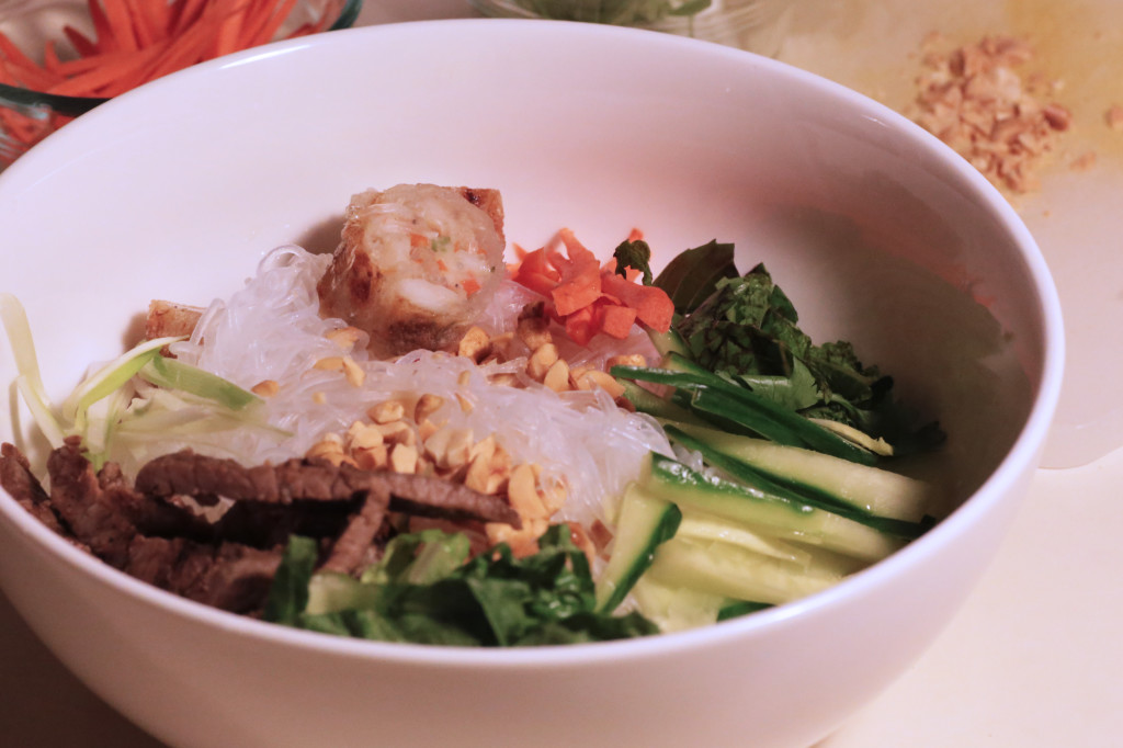 Chilled rice noodles are served with an assortment of chopped vegetables, lettuce, herbs, bbq beef, fried shrimp spring rolls  and garnished with dry roasted peanuts.